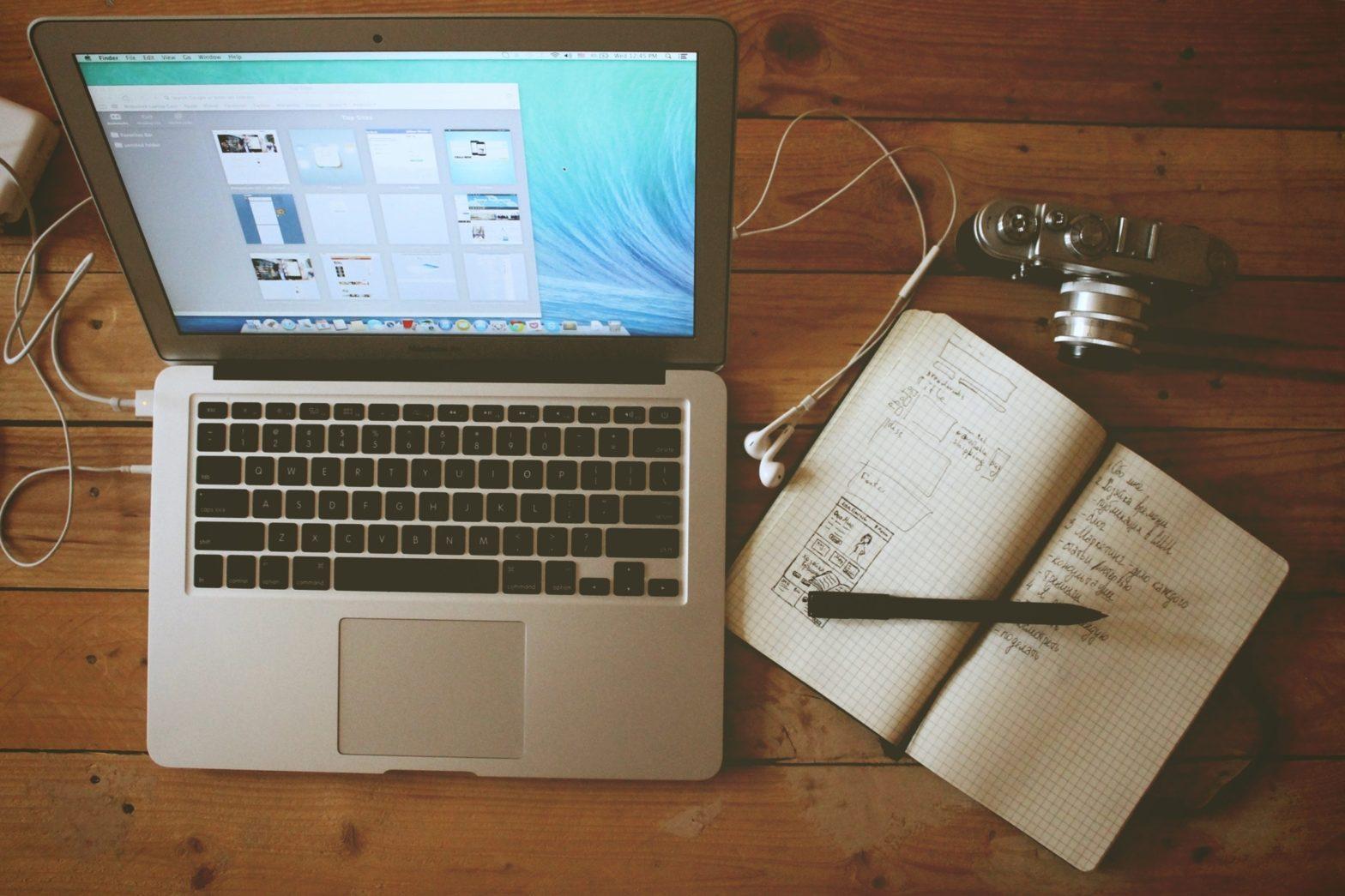 ordinteur écouteur appareil photo cahier ouvert et stylo posé sur un bureau