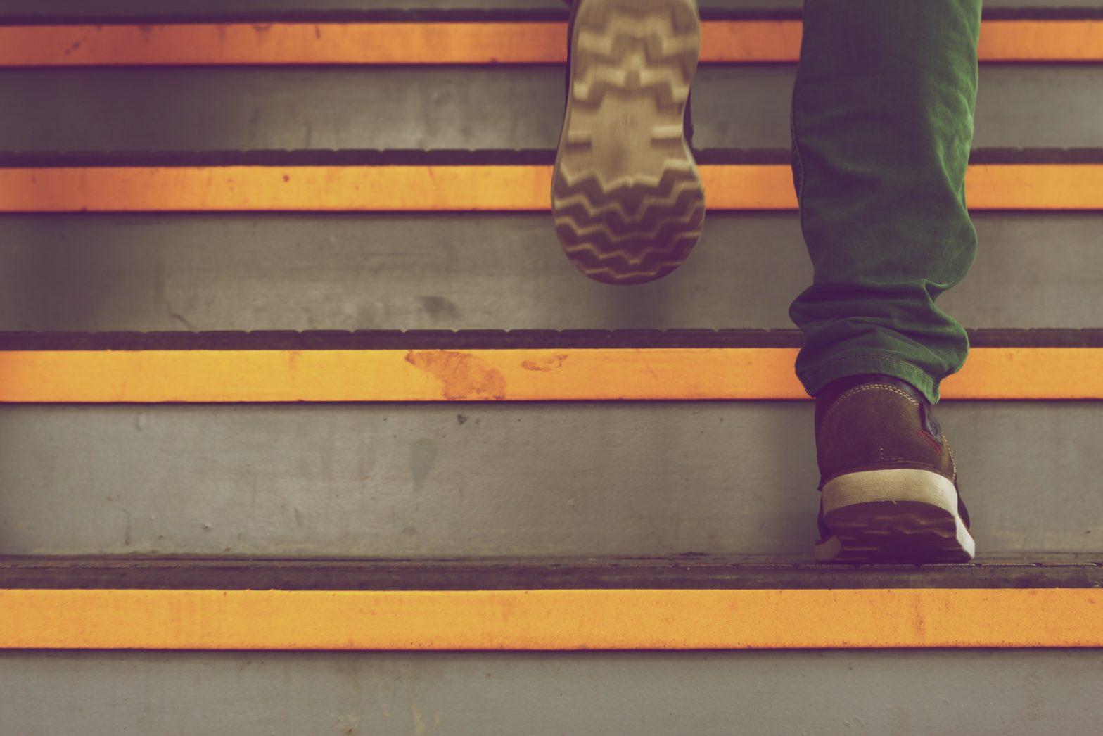 pied d'une personne qui monte les escaliers rapidement